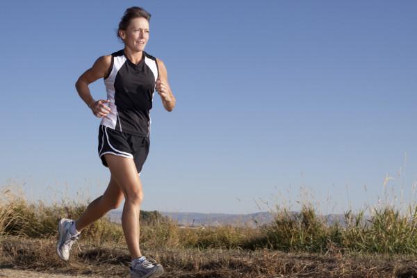 Imagem de uma mulher correndo em uma área de natureza.