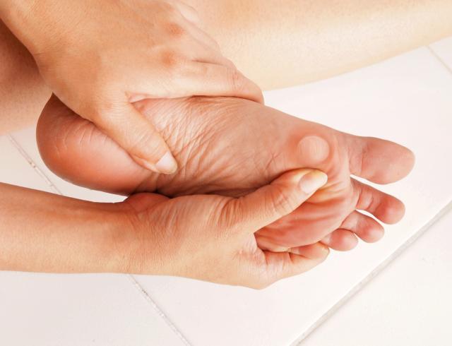 Imagem ilustrativa de uma pessoa segurando um pé com uma bolha no dedo