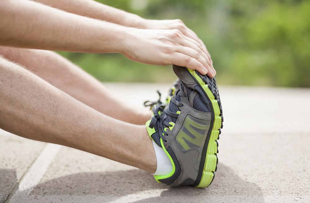 Imagem de uma pessoa alongando seus pés.