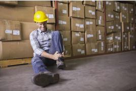 Foto de um homem com dores no tornozelo sentado no piso de uma fábrica.