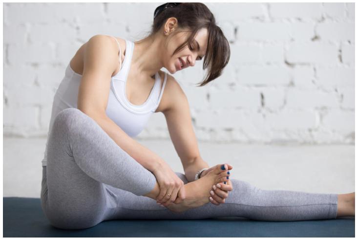 Mulher segurando o pé direito com sinais de dor