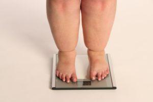Pessoa obesa se pesando na balança.
