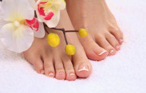 pés com flor e unha francesinha