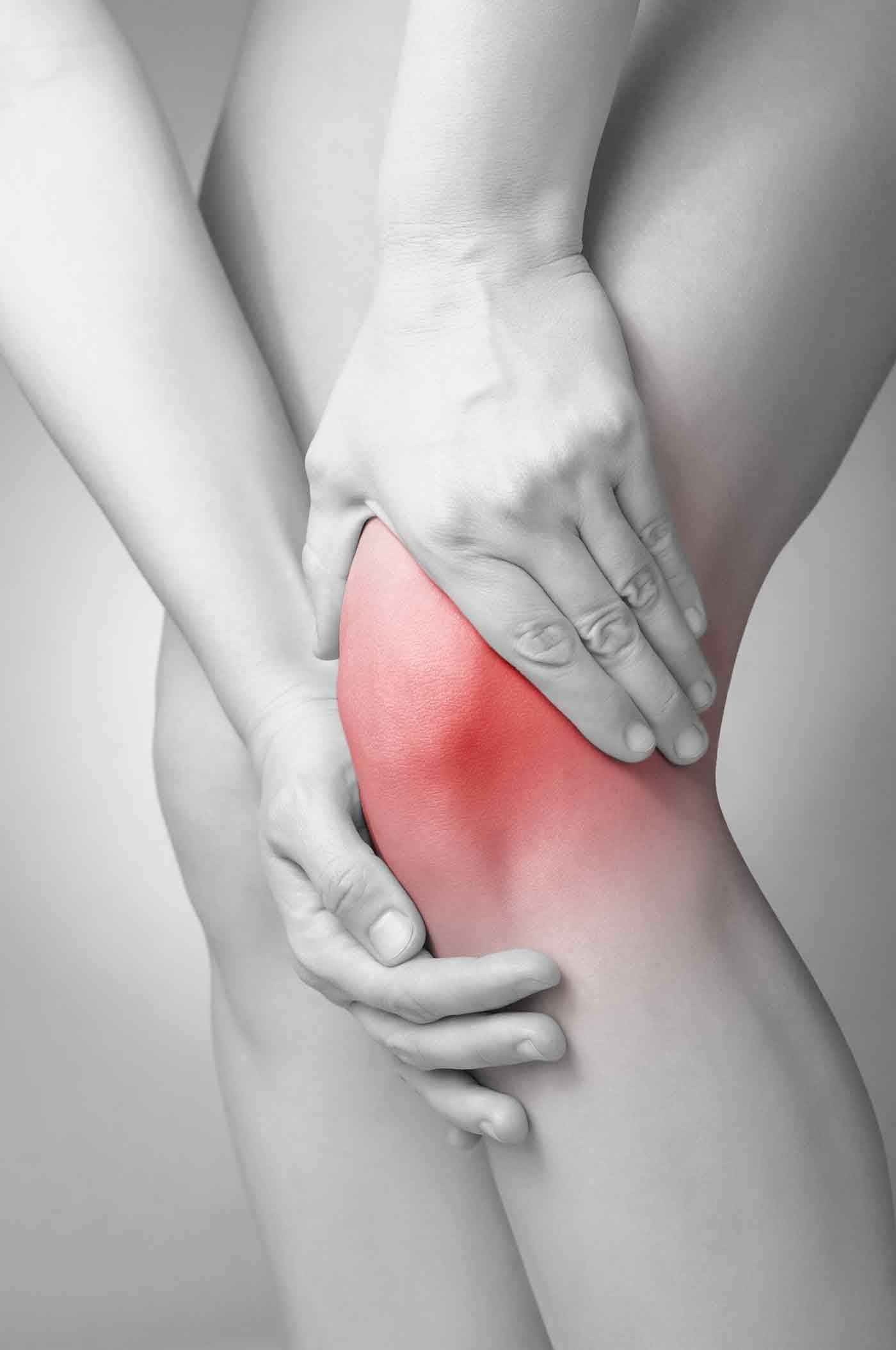 Mulher massageando seu joelho dolorido