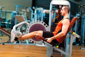 Homem jovem em uma cadeira flexora de academia