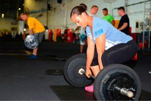 Mulher jovem levantando peso na academia
