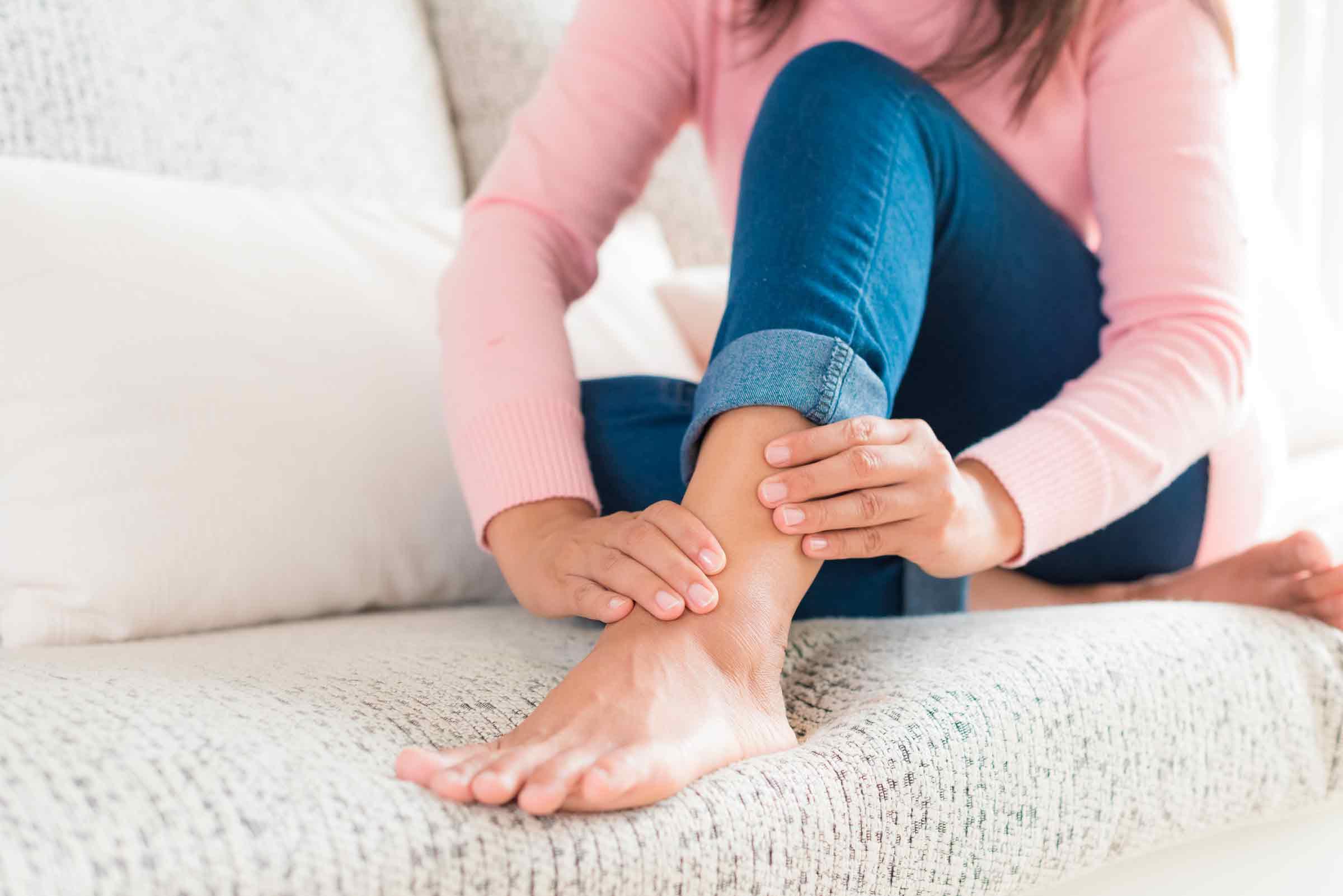 Imagem de uma mulher sentada em um sofá e se segurando o seu tornozelo dolorido